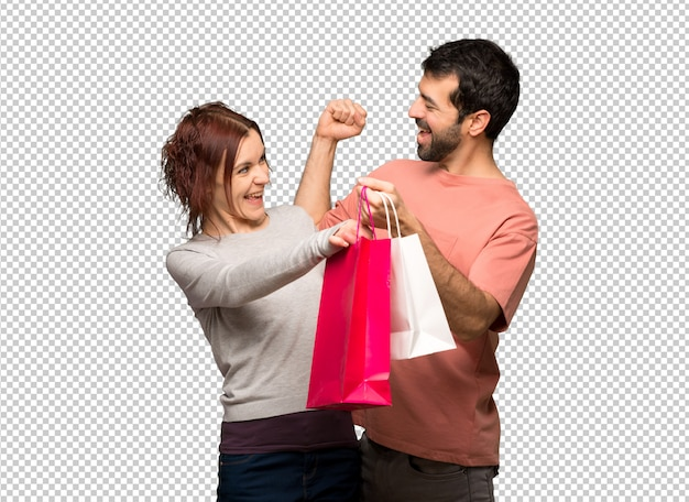 Couple in valentine day holding shopping bags in victory position