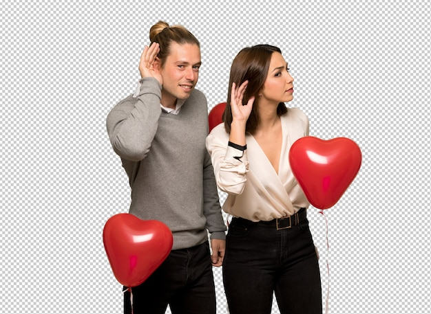 Couple in valentine day listening to something by putting hand on the ear