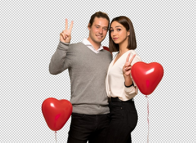 Couple in valentine day smiling and showing victory sign with both hands