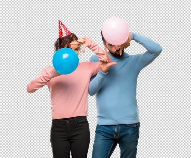Пара с воздушными шарами и день рождения шляпы фокусировки лица. обрамляющий символ
