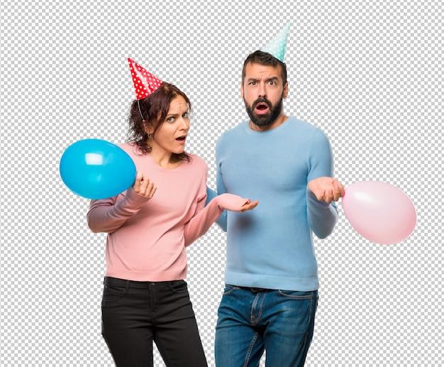 Пара с воздушными шарами и шляпами рождения с сомнениями и с запутанным выражением лица