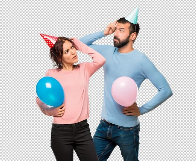 Пара с воздушными шарами и шляпами рождения с сомнением и с запутанным лицом, царапая голову