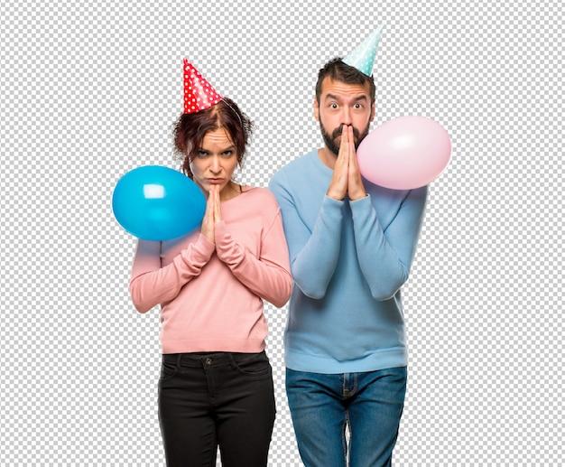 Пара с воздушными шарами и шляпами рождения держит ладонь вместе. человек просит чего-то