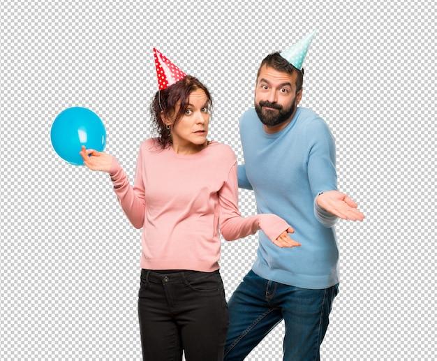Пара с воздушными шарами и шляпами на день рождения, делая сомнения в жесте при поднятии плеч