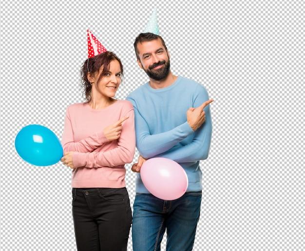 제품을 제시하기 위해 손가락으로 측면을 가리키는 풍선 및 생일 모자와 커플