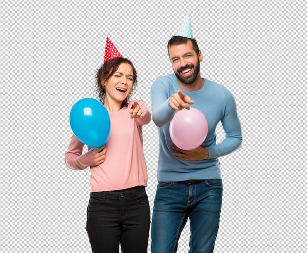풍선 및 생일 모자와 사람을 손가락으로 가리키는 많은 웃음을