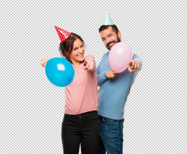 풍선과 생일 모자 커플은 웃고있는 동안 손가락을 가리 킵니다