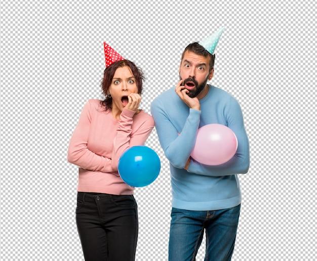Пара с воздушными шарами и шляпами на день рождения удивлена и шокирована, глядя вправо