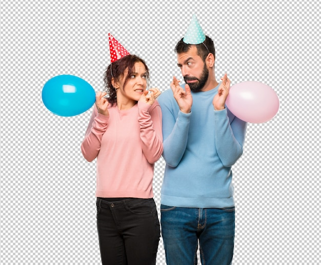 Пара с воздушными шарами и шляпами рождения с пальцами, пересекающими и желающими лучшего