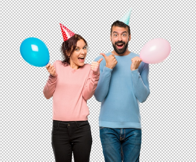 Couple with balloons and birthday hats giving a thumbs up gesture
