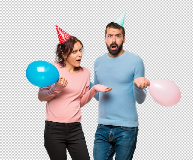 Couple with balloons and birthday hats having doubts and with confuse face expression