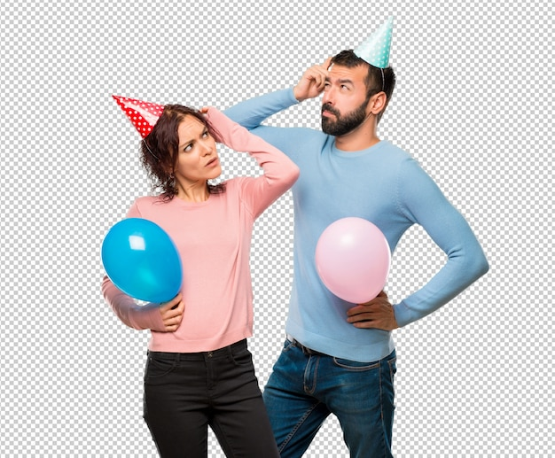 Couple with balloons and birthday hats having doubts and with confuse face while scratching head