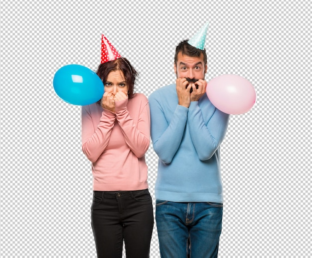 Couple with balloons and birthday hats is a little bit nervous and scared putting hands to mouth
