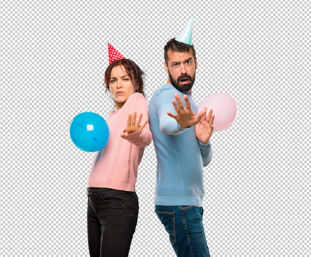 Couple with balloons and birthday hats is a little bit nervous and scared stretching hands