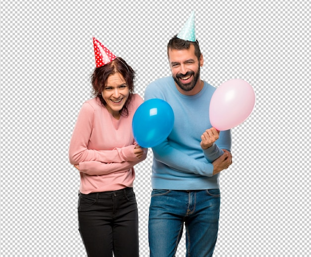 Couple with balloons and birthday hats keeping the arms crossed while smiling