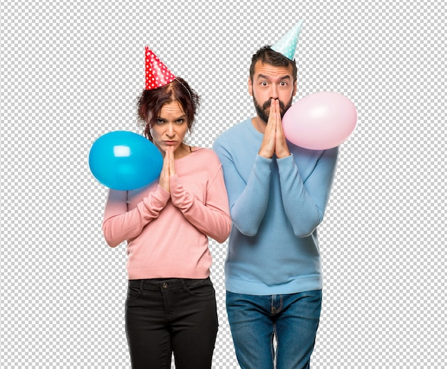 Couple with balloons and birthday hats keeps palm together. person asks for something