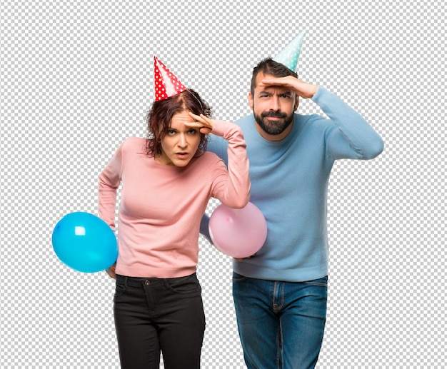 Couple with balloons and birthday hats looking far away with hand to look something