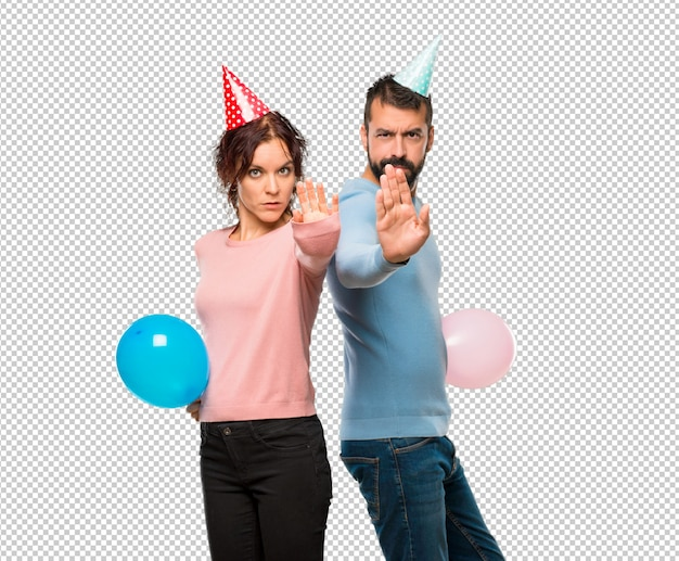 Couple with balloons and birthday hats making stop gesture with her hand denying