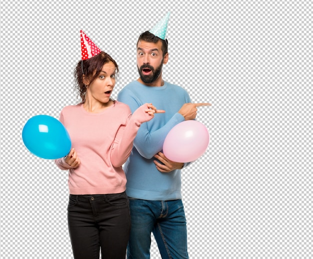 Couple with balloons and birthday hats pointing finger to the side with a surprised face