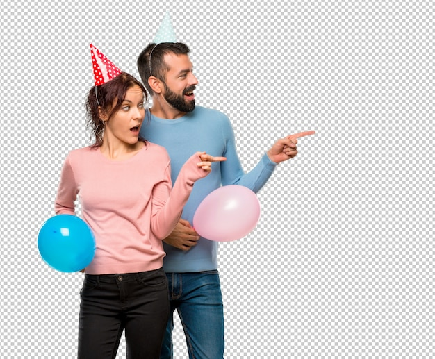 Couple with balloons and birthday hats pointing finger to the side
