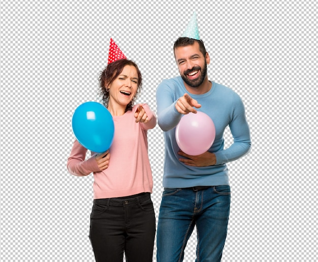 Couple with balloons and birthday hats pointing with finger at someone and laughing a lot