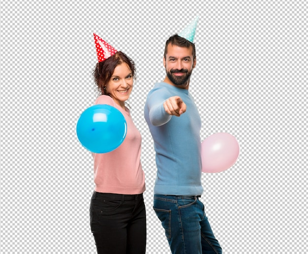Couple with balloons and birthday hats points finger at you with a confident expression