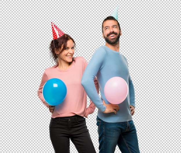 Couple with balloons and birthday hats posing with arms at hip and laughing