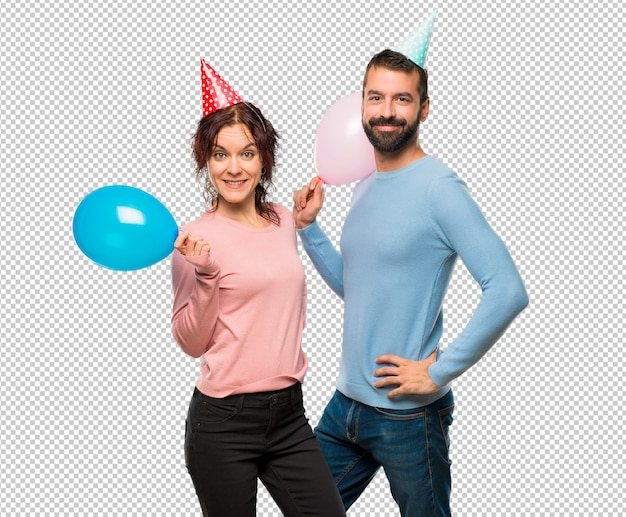 Couple with balloons and birthday hats posing with arms at hip and smiling