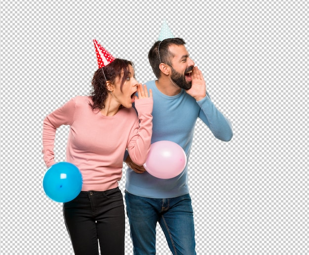 Couple with balloons and birthday hats shouting to the lateral and announcing something