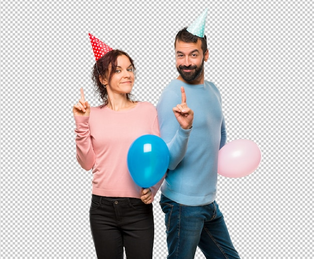 Couple with balloons and birthday hats showing and lifting a finger in sign of the best