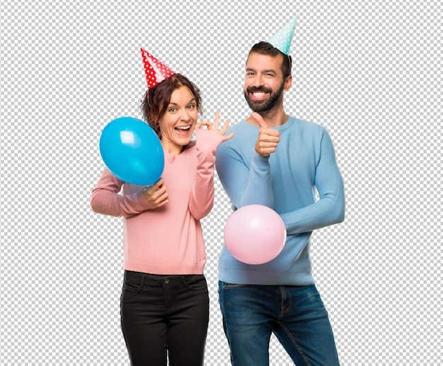 Couple with balloons and birthday hats showing ok sign and giving a thumb up gesture