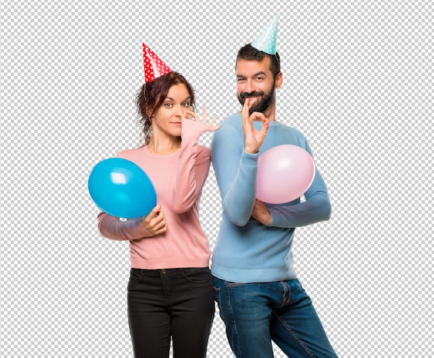 Couple with balloons and birthday hats showing an ok sign with fingers