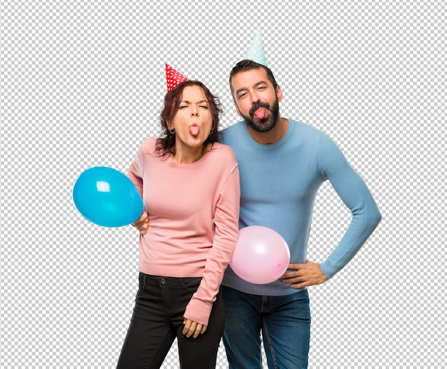 Couple with balloons and birthday hats showing tongue at the camera having funny look