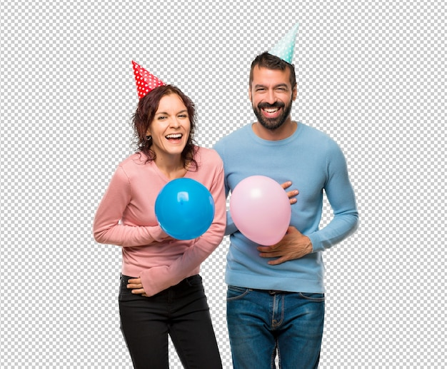 Couple with balloons and birthday hats smiling a lot while putting hands on chest