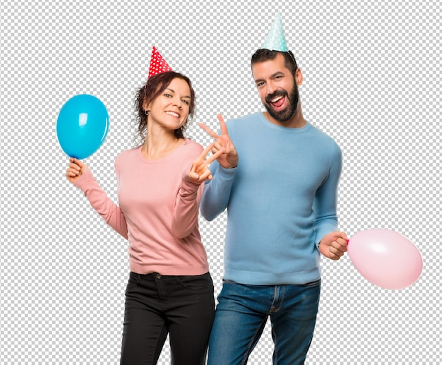 Couple with balloons and birthday hats smiling and showing victory sign with both hands