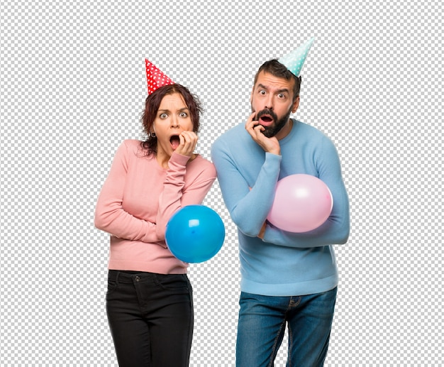 Couple with balloons and birthday hats surprised and shocked while looking right