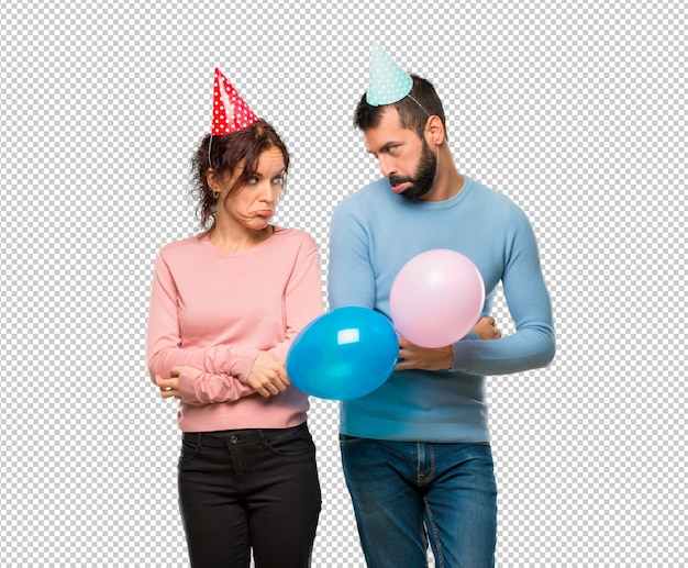 Couple with balloons and birthday hats with sad and depressed expression. serious gesture