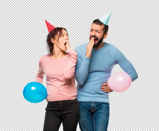 Couple with balloons and birthday hats yawning and covering mouth with hand. sleepy expression