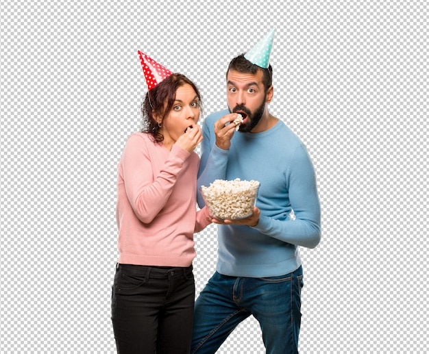Couple with birthday hats and eating popcorns