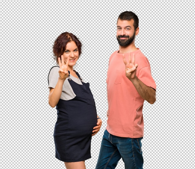 Couple with pregnant woman happy and counting three with fingers