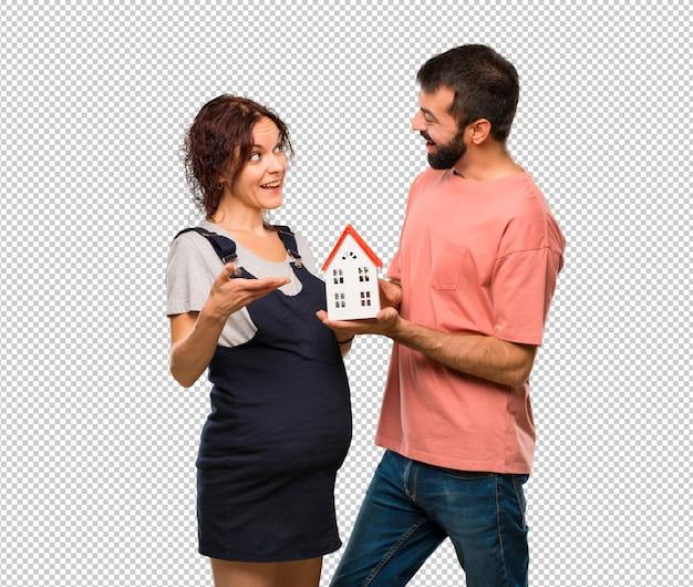 小さな家を持つ妊婦とのカップル