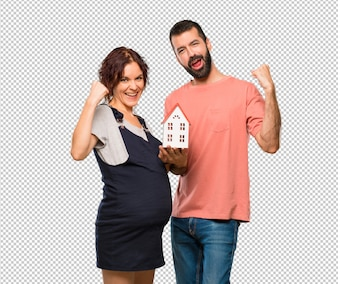 Couple with pregnant woman holding a little house