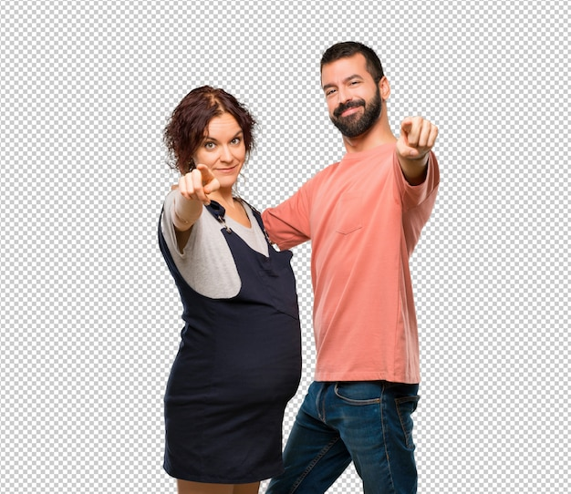 Couple with pregnant woman points finger at you with a confident expression