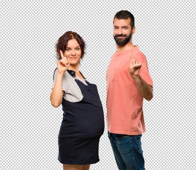 임신 한 여자가 표시하고 최고의 기호로 손가락을 들어 올리는 커플