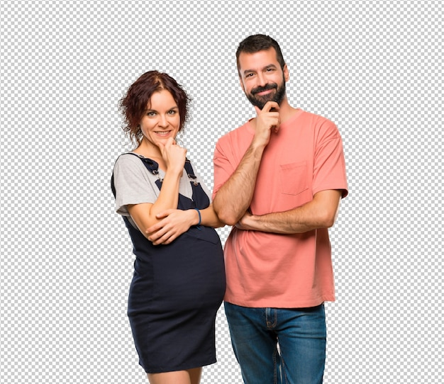 Couple with pregnant woman smiling and looking to the front with confident face