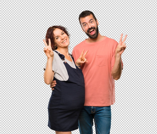 Couple with pregnant woman smiling and showing victory sign with both hands