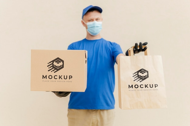 Курьер держит коробку и макет сумки
