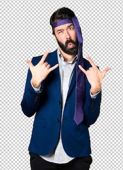 Crazy and drunk businessman making horn gesture