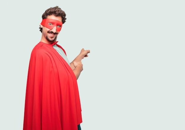 Сумасшедший мужчина, как супер герой, улыбающийся и указывающий вверх обеими руками