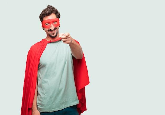 Сумасшедший, как супер герой, счастливо улыбающийся и указывающий вперед, выбирая тебя
